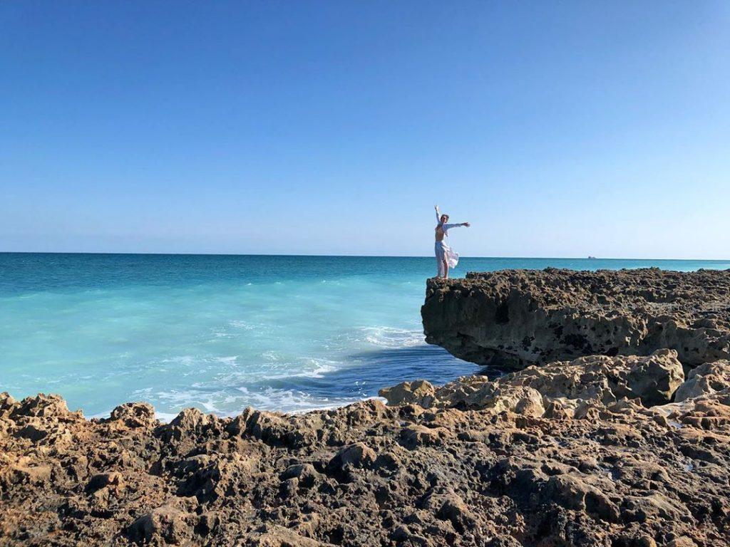 Woman Standing at the ocean edge enjoying the sun